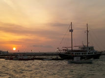 风船的帆柱反对美丽的日落天空的在米科诺斯岛旧港口  库存照片