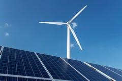 风车和太阳电池板在蓝天在白天 图库摄影