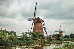 风车和庭院一条大运河的银行的在一多云天在小孩堤防 图库摄影