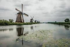 风车和灌木在一条大运河的银行在一多云天在小孩堤防 库存照片