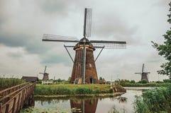 风车和灌木在一条大运河的银行在一多云天在小孩堤防 免版税库存图片