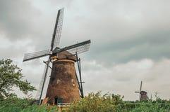 风车和灌木在一条大运河的银行在一多云天在小孩堤防 库存图片