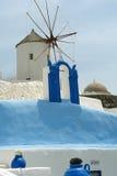 风车和蓝色墙壁在圣托里尼海岛上 免版税库存照片