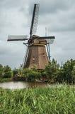 风车和高灌木在一条大运河的银行在一多云天在小孩堤防 图库摄影