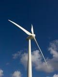 风车在阳光下反对与软的云彩的蓝天 免版税库存图片