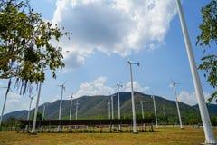 风车白色岗位和太阳能电池在有绿色山的,蓝天草围场镶板技术引起干净的可再造能源 免版税库存照片