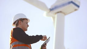 风车的能量工程师与片剂一起使用在日落 环境 股票录像