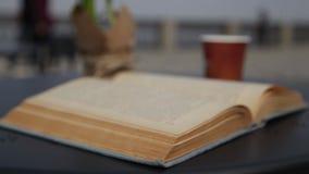 风转动一本旧书的页 早晨咖啡录影与户外一个老法院记录的 影视素材