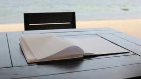风转动说谎在桌上的一个空白的笔记薄的页 股票录像