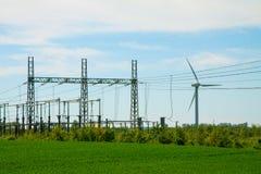 风轮机农厂和分站电在风景的输电线与绿草和蓝天 库存照片