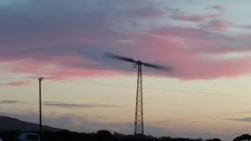 风轮机在转动的康沃尔郡,由海洋的日落 免版税库存图片