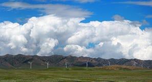 风轮机或风车在绿草调遣与山脉和多云蓝天背景 免版税图库摄影