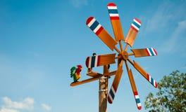 风轮机木油漆泰国的旗子蓝天背景的 免版税库存照片