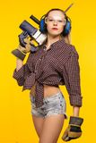风镜和耳机的美丽的年轻女人值得拿着穿孔器钻子被隔绝在黄色背景 免版税库存照片