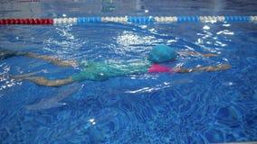 风镜泳装盖帽和鸭脚板的儿童女孩训练在水池的游泳 股票视频