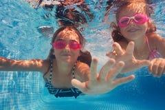 风镜的两个愉快的女孩游泳在水下的 免版税库存图片
