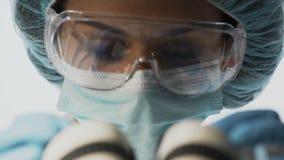 风镜的实验室科学家与显微镜,举办的医学研究一起使用 股票视频