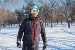 风镜的愉快的挡雪板获得乐趣,使用与雪在Th 库存图片