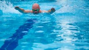 风镜的年轻人游泳使用蝴蝶技术 免版税库存照片
