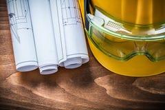 风镜计划卷和安全帽在棕色木委员会 图库摄影