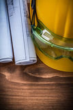 风镜建筑计划和安全帽在棕色木板 库存照片
