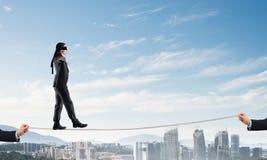 风险支持和协助的企业概念与平衡在绳索的人 库存照片