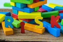 风险概念有在崩溃的五颜六色的木字母表风险求爱 免版税库存照片