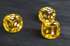 风险概念-演奏在黑木背景的模子 打与模子的一场比赛 黄色赌博娱乐场模子卷 把滚切成小方块 图库摄影
