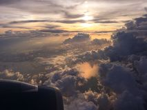 风雨如磐的云彩和金黄日落通过飞机窗口 免版税库存照片