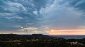 风雨如磐的天空、日出海上和风景在圣洁山Athos附近 库存图片