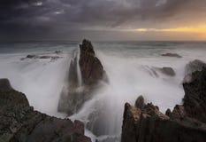 风雨如磐的日出和波浪碰撞在海堆 图库摄影