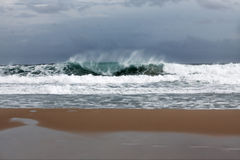 风雨如磐的波浪临近海滩 库存图片