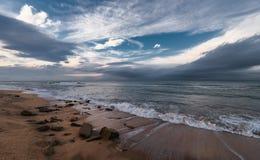 风雨如磐的海和五颜六色的云彩在天际 免版税库存照片