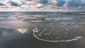 风雨如磐的海在与白色的冬天挥动击碎-葡萄酒影片lo 免版税库存照片