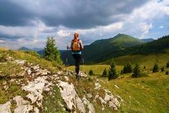 风雨如磐,象打雷天空 与山峰顶的看法  运动的红色头发女孩上升由与岩石的小山决定 极其体育运动 免版税图库摄影