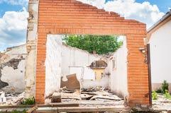 飓风或地震在被破坏的老房子的灾害损伤内部遗骸在有倒塌的墙壁、屋顶和砖的城市 库存图片