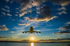 飞机上升,飞行在往太阳的海在日落 免版税库存照片