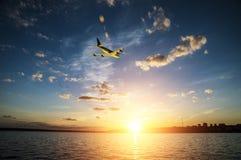 飞机上升,飞行在往太阳的海在日落 库存图片