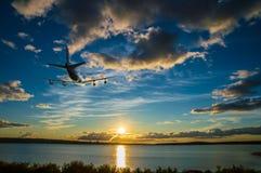 飞机上升,飞行在往太阳的海在日落 库存照片