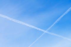 飞机两条相交的结露轨道在清楚的蓝天的 您的文本的地方,为背景使用 库存图片