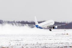 飞机从恶劣天气的积雪的跑道机场离开在雪风暴,一阵强风期间在冬天 库存图片