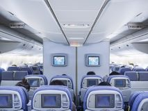 飞机内部飞行在船上与乘客座位行屏幕显示器 免版税库存图片