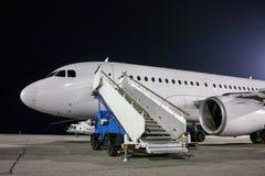 飞机和乘客搭乘在夜机场围裙的步车 免版税库存图片