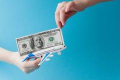 飞机和美元在妇女手上在蓝色背景 r 免版税库存图片