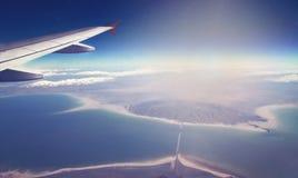飞机和翼的图象有海、山和海岸线的 Horizont线和日出 免版税库存照片