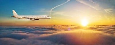 飞机在云彩上的喷气式飞机飞行在美好的日落光 库存照片
