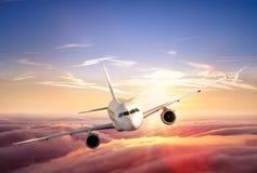 飞机在云彩上的喷气式飞机飞行在美好的日落 图库摄影