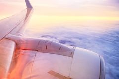 飞机在云彩上的翼飞行在日落 选择聚焦 文本的空间 库存图片