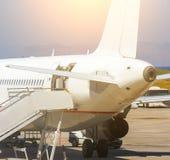 飞机在地勤人员为服务的机场 与门户开放主义的背面图,定调子 库存图片