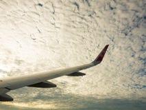 飞机在天空和白色云彩飞过在中间 免版税库存图片